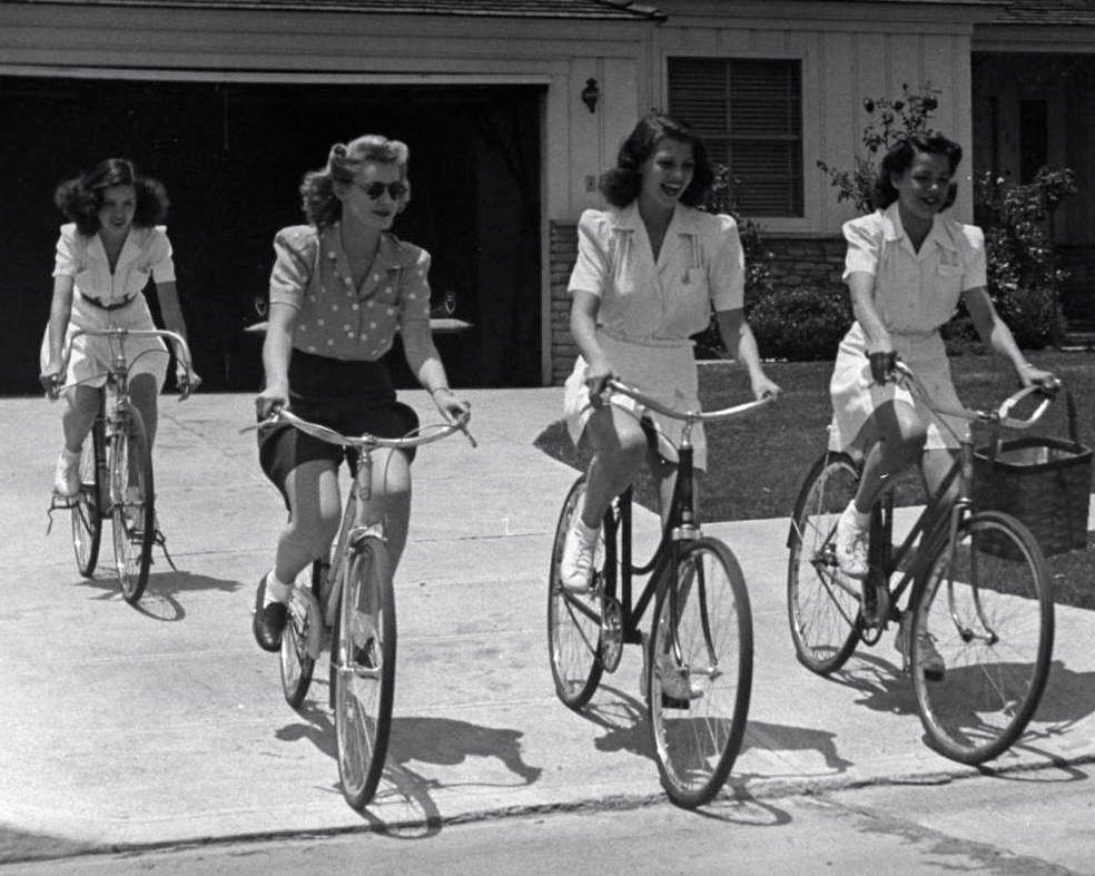 Minerva Griswold, Jane Hopkins, Rita Hayworth and Virginia Hovey ride bikes.
