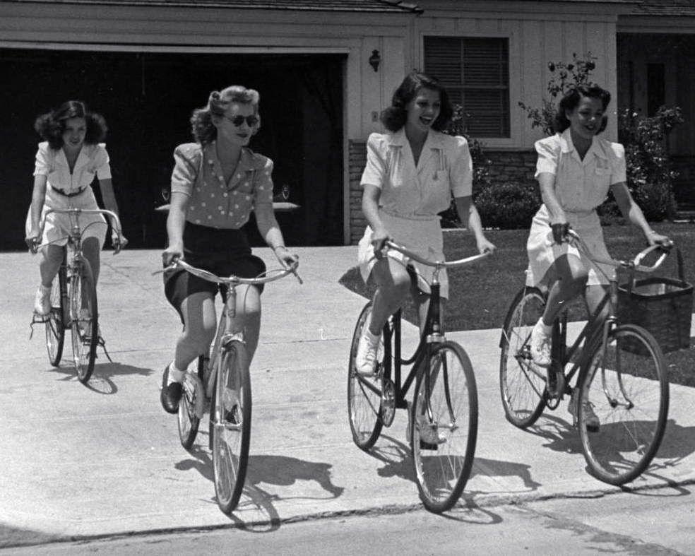 Minerva Griswold, Jane Hopkins, Rita Hayworth and Virginia Hovey ride bikes.